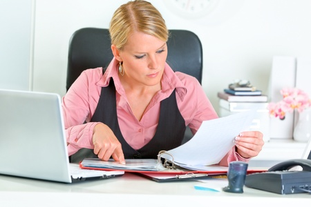 centrality: Concentrated modern business woman sitting at office desk and working with financial documents