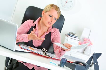 dissatisfied: Sitting at office desk modern business woman dissatisfied with bad results of work