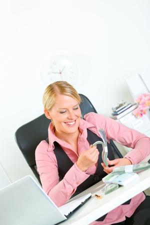 contando dinero: Mujer de negocios modernos sentado a la mesa de oficina y contando dinero