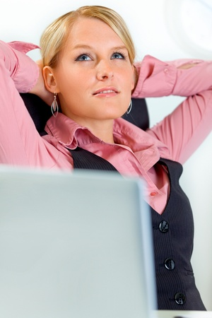 Pleased modern business woman relaxing at office photo