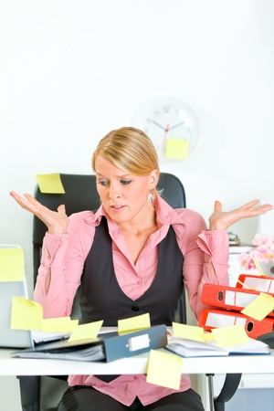 tasks: Shocked by set of tasks modern business woman sitting at workplace covered with sticky notes
