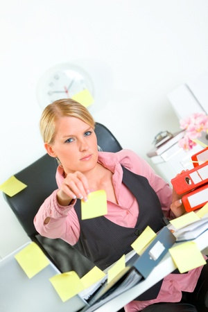 Stressful modern business woman sitting at workplace and stretches out hand with blank sticky notes  Stock Photo - 9665672