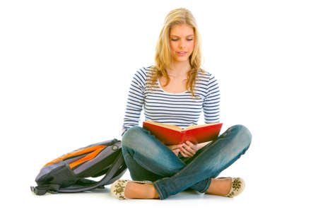 Pensive teengirl with schoolbag  sitting on floor and reading book isolated on white   photo