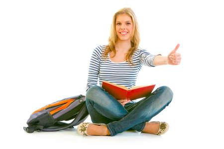 classbook: Showing thumbs up gesture smiling young girl with schoolbag and book sitting on floor isolated on white   Stock Photo