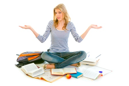 classbook: Teengirl with surprise expression on face sitting on floor surrounded by books isolated on white