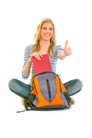 classbook: Sitting on floor smiling girl geting book from schoolbag and showing thumbs up gesture isolated on white