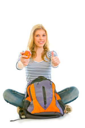 Smiling girl sitting on floor with schoolbag holding apple in hand and showing thumbs up gesture isolated on white Stock Photo - 9665562