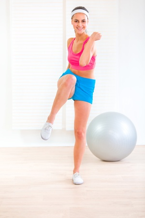 Smiling healthy young girl doing fitness exercises at living room Stock Photo - 9665898