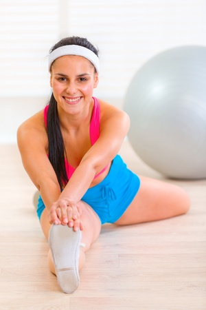 Smiling gymnastic young girl doing stretching exercises  at living room Stock Photo - 9665947