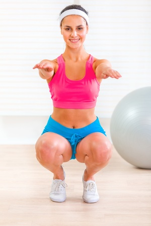Cheerful fitness young girl doing  exercises at living room Stock Photo - 9665946