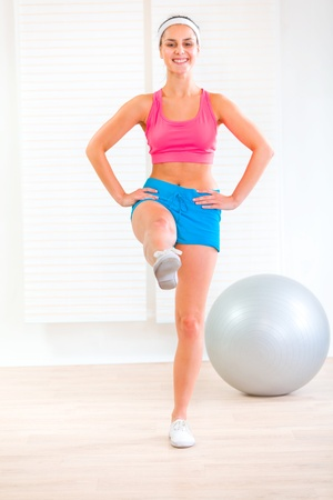 Smiling fitness young girl doing exercises at living room Stock Photo - 9665886