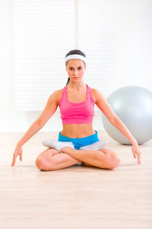 Concentrated young girl practising yoga exercises on floor at living room   photo