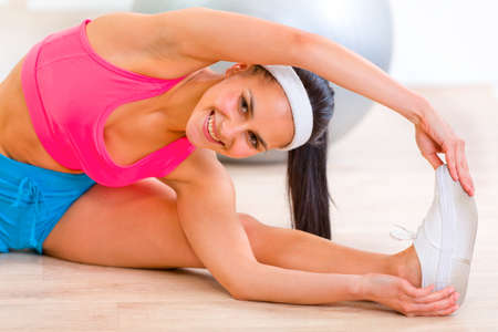 Smiling flexible young girl stretching legs on floor at living room Stock Photo - 9666015