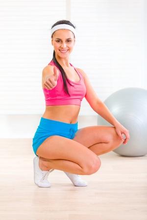 squatting: Sonriente joven cuclillas abajo y mostrando pulgar arriba gesto de aptitud