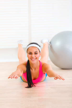 Smiling flexible young girl making gymnastics exercise at living room Stock Photo - 9665933