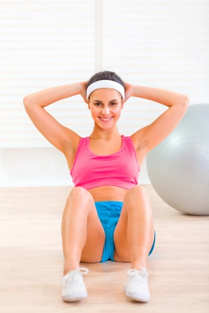 Smiling fitness young girl doing abdominal crunch on floor at living room   photo