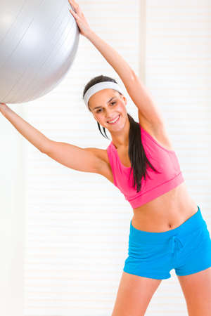 Happy healthy young girl doing  exercises with fitness ball  at living room