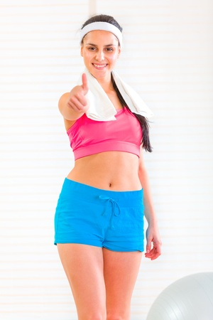 Smiling fit girl with towel around neck showing thumbs up gesture