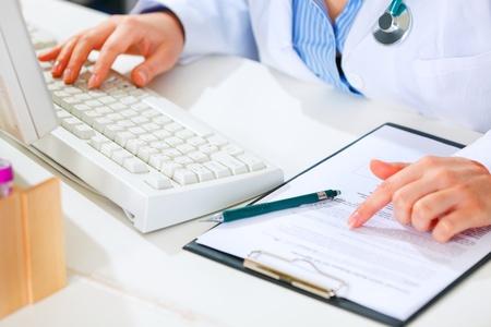 Office uniforms: Doctor en medicina mujer trabajando en mesa de oficina. Detalle.  Foto de archivo