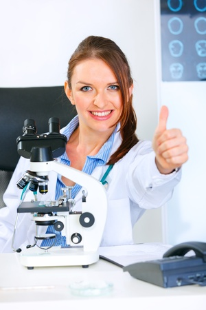 Smiling medical doctor woman using microscope in laboratory and showing thumbs up gesture Stock Photo - 9665999