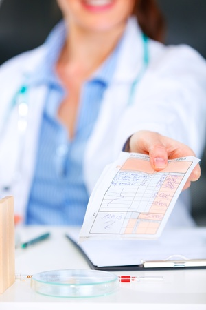 Doctor woman sitting at office table and giving medical prescription. Closeup. Stock Photo - 9665994