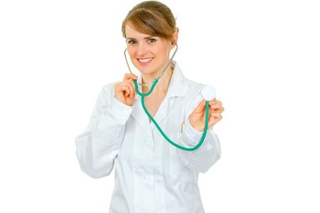 Smiling medical female doctor holding up stethoscope isolated on white Stock Photo - 9666087