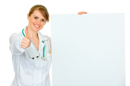 amiable: Smiling medical female doctor holding blank billboard and showing thumbs up gesture isolated on white  Stock Photo