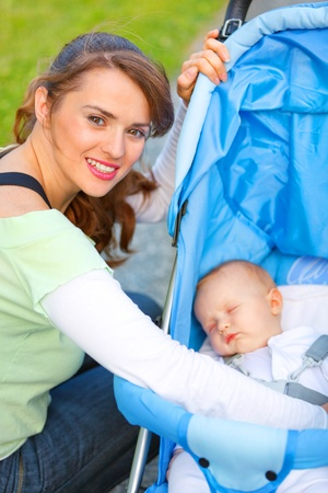 perambulator: Smiling young mother sitting near stroller and taking care about her baby
