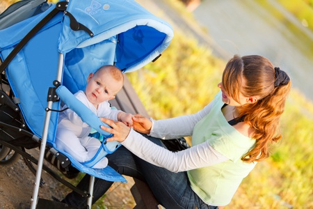 baby carriage: Happy young mother holding babys hand   Stock Photo