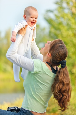 Happy young mother playing with laughing baby girl in park