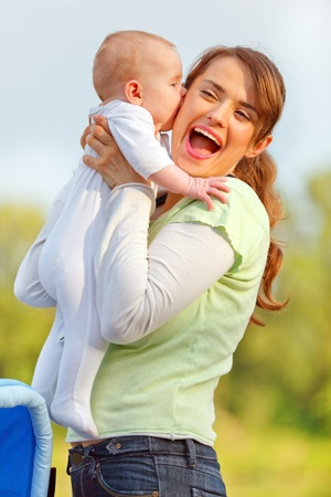 Baby girl kissing holding her happy mother