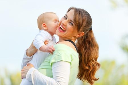 madre y bebe: Riendo joven madre abrazando a su beb� en las manos al aire libre Foto de archivo