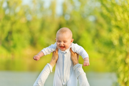 Mother's hands holding laughing baby girl against sunny leaves. Baby looking on mother. Stock Photo - 9792644