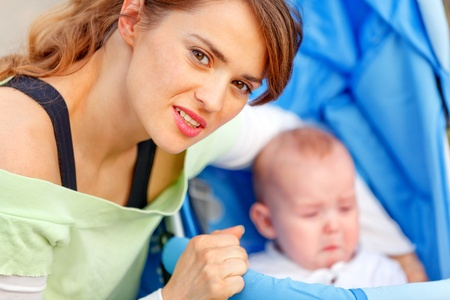 Caring young mother hugging sitting in stroller crying baby Stock Photo - 11640436