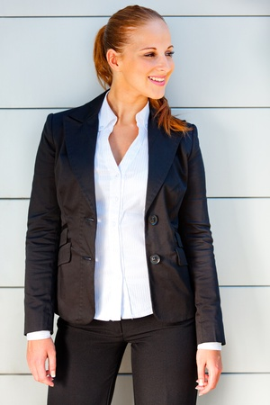 near side: Smiling modern business woman standing near office building and looking on side  Stock Photo