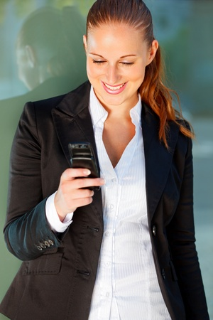 Smiling modern business woman near office building looking on mobile  photo