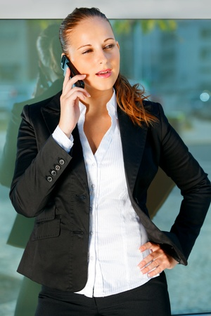 sagacious: Pensive modern business woman talking on mobile  near office building   Stock Photo