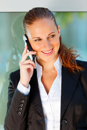 Portrait of modern smiling business woman talking on mobile at office building    photo