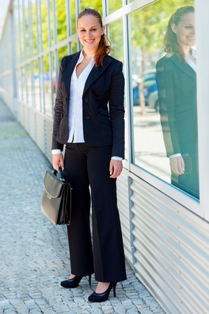 Full length portrait of smiling modern business woman with briefcase at office building  photo