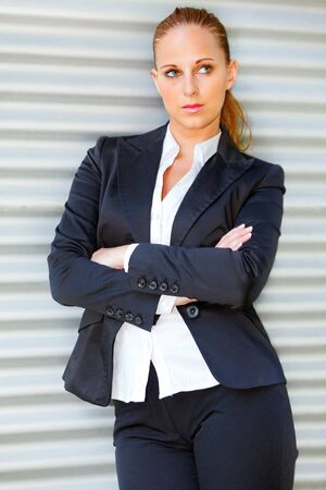 Concentrated modern business woman standing at office building and looking in corner  photo