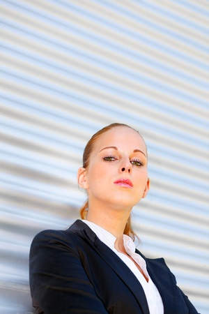 Proud modern business woman standing at office building  photo