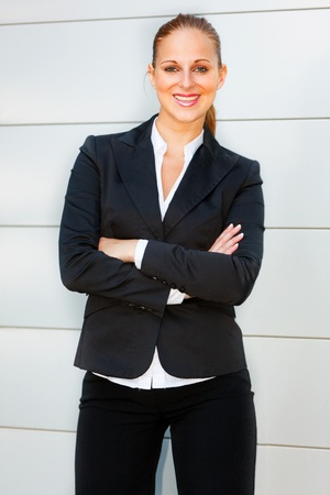Smiling modern business woman with crossed arms on chest standing at office building  photo