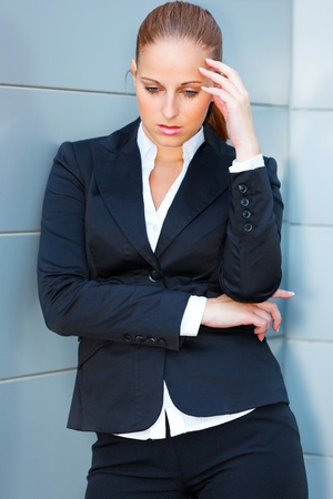 Pensive modern business woman with hand near head standing at office building  photo