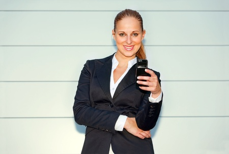 Smiling modern business woman holding mobile in hand near office building   photo