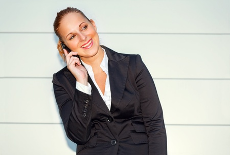 Pleased modern business woman talking on mobile near office building   photo