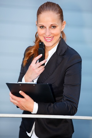Leaning on railing at office building  smiling modern business woman holding mobile and clipboard   photo