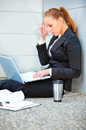 Concentrated modern business woman sitting on floor at office building  and using laptop  photo