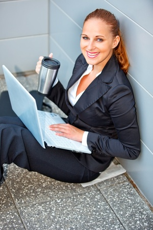 Smiling modern business woman with laptop and cup sitting on floor at office building    photo