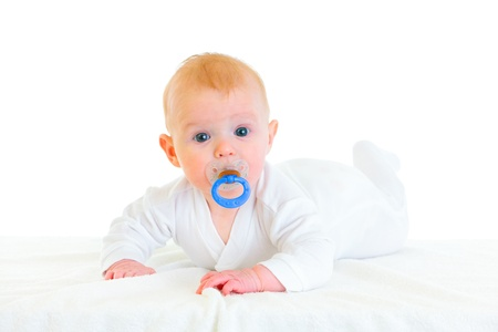 interrogatively: Sweet  four month old  baby girl with soother laying on diaper  Stock Photo