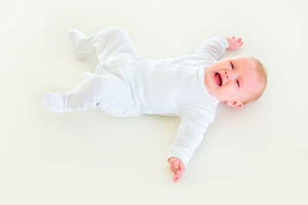 Crying four month old  baby girl laying on back